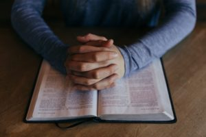Pray for Our Missionaries - Praying Hands over the Bible